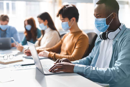 Photo pour New Normal Reality Rules, People And Workspace Concept. Group of diverse international people wearing disposable surgical masks studying and working sitting at desk, preparing project, using laptop - image libre de droit
