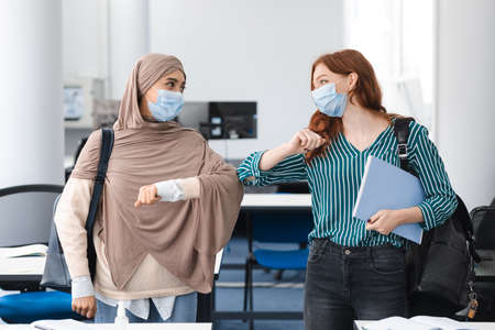 Photo pour Stop Spreading Virus Concept. Smiling diverse female students wearing protective face masks greeting each other and bumping elbows at classroom. Women standing indoors with backpack and notebooks - image libre de droit