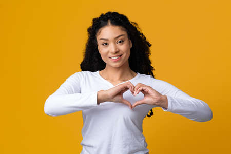 Photo pour Beautiful young black lady making heart gesture with hands near chest, making love sign at camera, friendly african american woman expressing kindness, standing on yellow studio background, copy space - image libre de droit