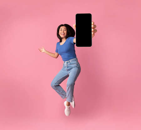 Photo pour Happy asian young woman showing empty smartphone screen while jumping up over pink studio background, collage, full size photo. Excited lady recommending nice and useful mobile application - image libre de droit