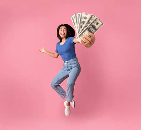 Photo for Full length portrait of a joyful young asian woman jumping up high and holding bunch of money banknotes, showing close to camera, celebrating win, isolated over pink studio background, collage - Royalty Free Image
