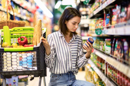 Photo pour Consumption And Consumerism. Portrait Of Young Woman With Shopping Cart In Market Buying Groceries Food Taking Products From Shelves In Store, Holding Glass Jar Of Sauce, Checking Label Or Expiry Date - image libre de droit