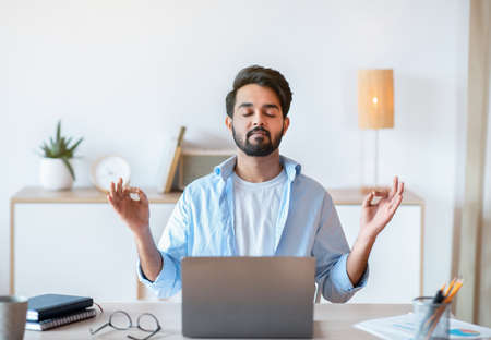Working Zen. Calm Eastern Businessman Meditating At Workplace In Office, Practicing Yoga While Sitting At Desk With Closed Eyes, Holding Hands In Mudra Gesture, Coping With Stress At Work, Empty Space