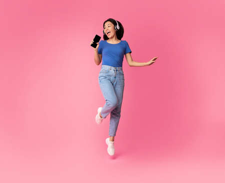 Photo pour Carefree Singer. Asian lady singing favorite song and using cell phone as a mic, dancing and jumping, wearing wireless headphones. Excited woman having fun at pink studio, enjoying sound, full length - image libre de droit