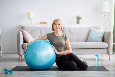 Photo pour Full length portrait of happy mature woman resting on yoga mat with fitness ball, smiling at camera indoors, free space. Cheerful senior lady taking break from her domestic training - image libre de droit