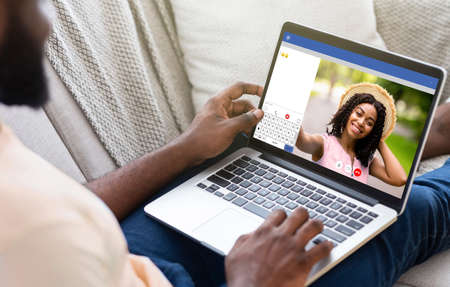 Photo for Young black man communicating to his girlfriend on video chat, using laptop computer for distance conversation at home. Millennial guy having videoconference with his wife, indoors - Royalty Free Image