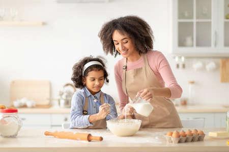Photo pour Happy black woman and daughter making pastry in kitchen - image libre de droit