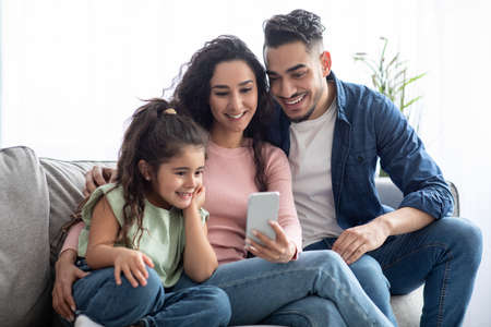 Foto für Happy arabic family of three using smartphone at home, relaxing on couch - Lizenzfreies Bild