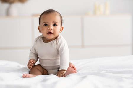 Foto für Cute little African American infant sitting on bed - Lizenzfreies Bild