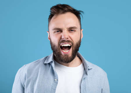Photo pour Enraged bearded guy shouting in anger, expressing his aggression over blue studio background - image libre de droit