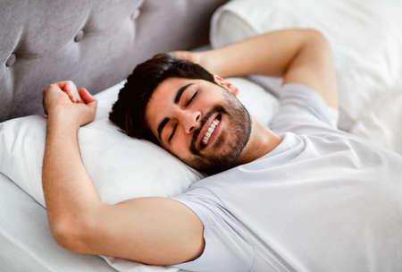 Photo pour Happy wellslept arab man awakening and stretching hands lying in modern comfy bed at home - image libre de droit