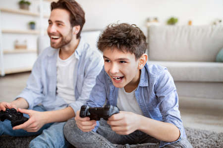 Photo for Quarantine entertainment. Overjoyed dad and son competing for win on gamepad at home, spending weekend together - Royalty Free Image