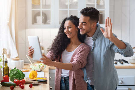 Photo pour Modern Muslim Couple Making Video Call With Digital Tablet In Kitchen - image libre de droit