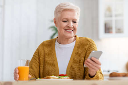 Photo for Smiling elderly woman using mobile phone while having lunch, closeup - Royalty Free Image