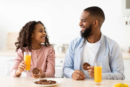 Photo for Cheerful african american daughter and dad having breakfast - Royalty Free Image