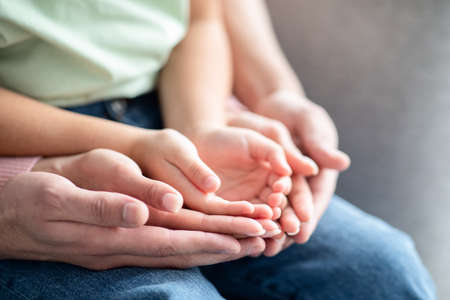 Photo for Closeup Shot Of Mom, Dad And Child Placing Their Hands Together - Royalty Free Image