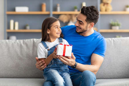 Photo pour Loving girl celebrating fathers day, greeting excited dad with present - image libre de droit