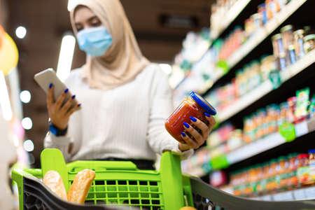 Foto für Muslim Lady Using Phone Buying And Scanning Food In Supermarket - Lizenzfreies Bild