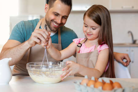 Photo pour Cheerful Father And Daughter Cooking Pancakes Making Dough In Kitchen - image libre de droit