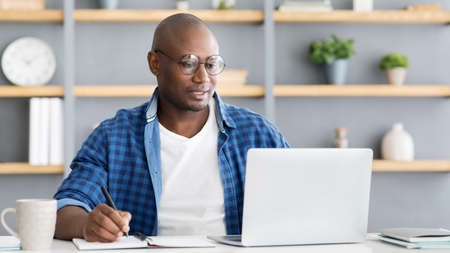 Photo pour African american entrepreneur working on laptop and taking notes, making business report while sitting at home office - image libre de droit