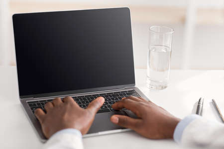 Photo for Online consultation. Unrecognizable african american doctor using laptop computer with empty screen, free space - Royalty Free Image