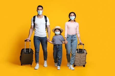 Photo pour Travel During Pandemic. Arab Tourists Family Wearing Protective Masks Walking With Suitcases - image libre de droit