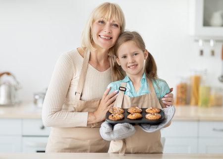 Photo pour Happy senior woman and her granddaughter preparing cookies - image libre de droit