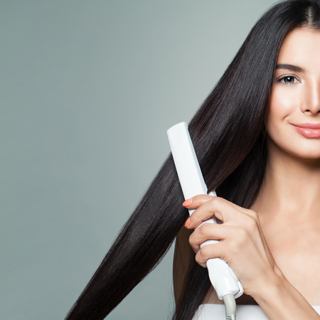 Photo pour Beautiful Woman with Long Straight Hair Using Hair Straightener. Cute Smiling Girl Straightening Healthy Brown Hair with Flat Iron on Gray Background. Closeup Portrait - image libre de droit