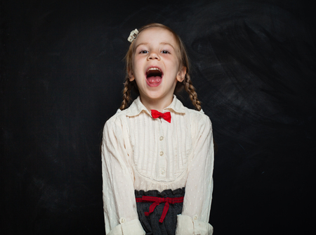Foto de Happy Child Girl Laughing on Blackboard Background. Kid Creativity and Education Concept - Imagen libre de derechos