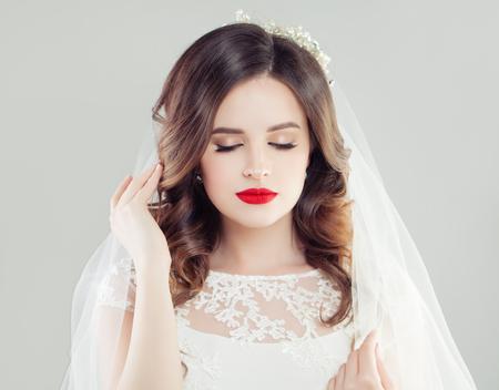 Foto de Beautiful bride woman with red lips makeup, bridal hair and white veil - Imagen libre de derechos