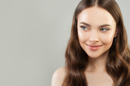 Photo pour Portrait of cheerful woman with clear skin and healthy curly hair on gray background. Beautiful face close up. Skincare and facial treatment concept - image libre de droit
