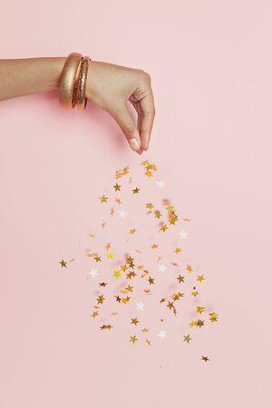 Photo pour Beautiful female hand streams sparkling gold stars confetti on pink background - image libre de droit