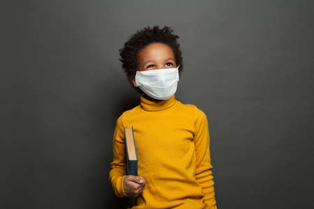 Photo pour Happy black child boy in medical protective face mask on blackboard background - image libre de droit