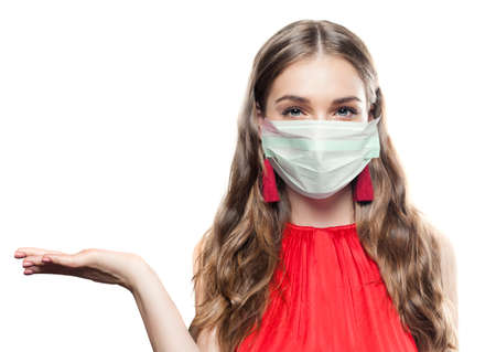 Photo pour Pretty woman in medical protective face mask holding empty open hand isolated - image libre de droit
