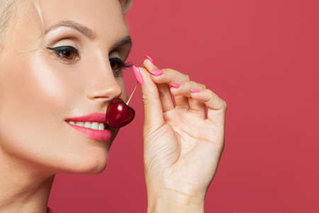 Photo pour Beautiful woman smiling closeup, smile with white teeth and red cherry berry in her hand - image libre de droit