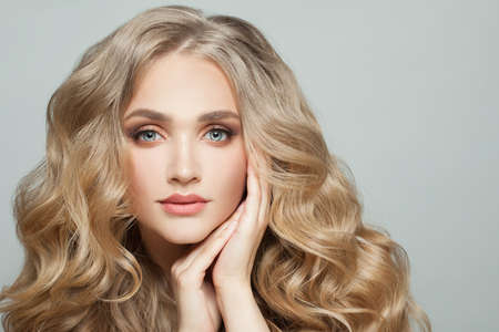 Photo pour Lovely woman model face with long healthy blonde curly hair on white - image libre de droit