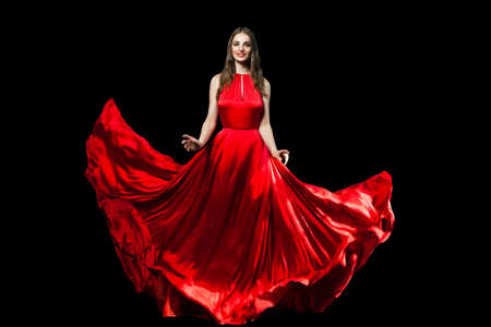 Photo pour Beautiful fashionable woman wearing red silky dress isolated on black background - image libre de droit