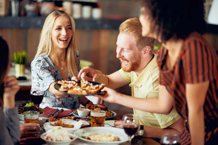 Photo pour Friends having dinner at restaurant. Multi ethnic group. - image libre de droit