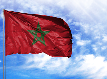 National flag of Morocco on a flagpole in front of blue sky.
