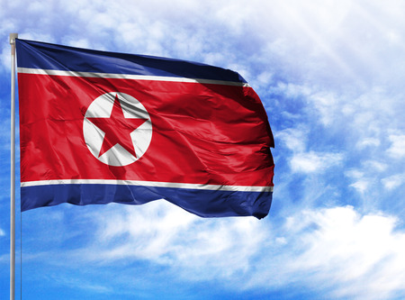 Photo pour National flag of North Korea on a flagpole in front of blue sky. - image libre de droit