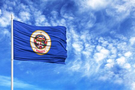 Foto per National flag State of Minnesota on a flagpole in front of blue sky - Immagine Royalty Free