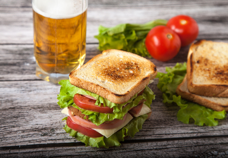 Photo pour sandwich, tomato, toast, salad and glass with beer on a on a woo - image libre de droit