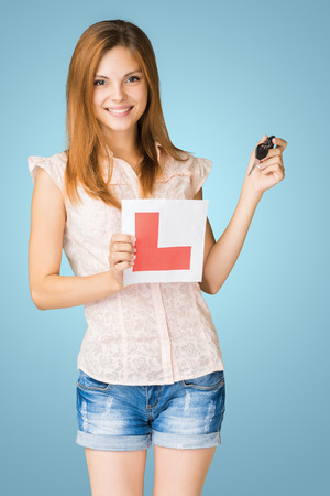 Young teenage learner driver holding L-plate and car keys, proud of passing her driving test at school.