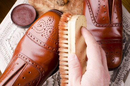 Brown leather shoes on table with polishing equipment