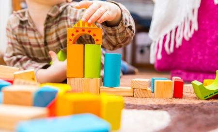 Foto de Small child playing with wooden blocks. Caucasian boy building with blocks - Imagen libre de derechos