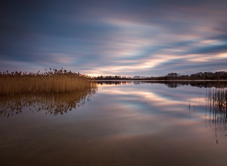 Lake landscape sunset photographed on long exposure. Polish lake in Mazury lake district.