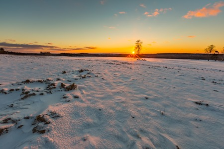 Beautiful winter sunset on fields landscape. Colorful landscape of sunset in winter.