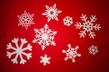 Photo pour Various paper cut out snowflakes on red background - image libre de droit