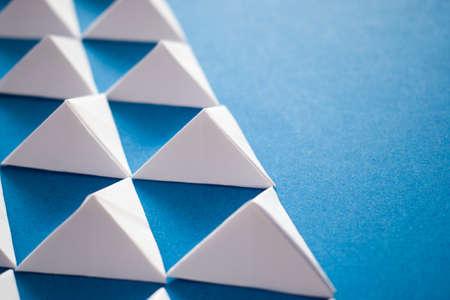Foto de Close up of white paper triangles on blue background - Imagen libre de derechos