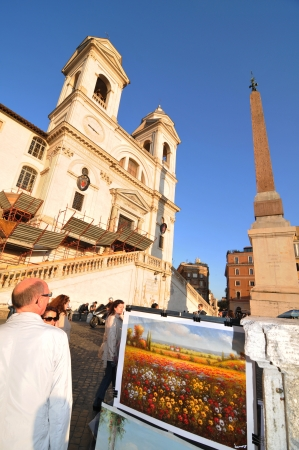 Rome, Italy - 30 March, 2012: Tourists enjoying the sunset in front of the church of the Santissima Trinit?ei Monti
